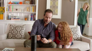 Eine Familie, die auf der Couch vor dem Amazon Echo sitzt